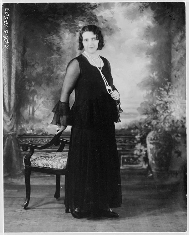 Black and white studio portrait of the singer La Bolduc. She is wearing a long black dress. She is standing in the middle of the picture, leaning on a chair in the Victorian style, in front of a painted background of classical style.