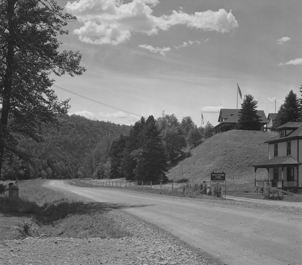 Black and white photograph taken along route 132 in the village of Routhierville in the Matapedia Valley. The road crosses a landscape of forests and mountains. On the right side of the photograph, a fishing club is perched on top of a hillock. On the side of the road sign indicates Cold Spring Camp, Private and No Admission
