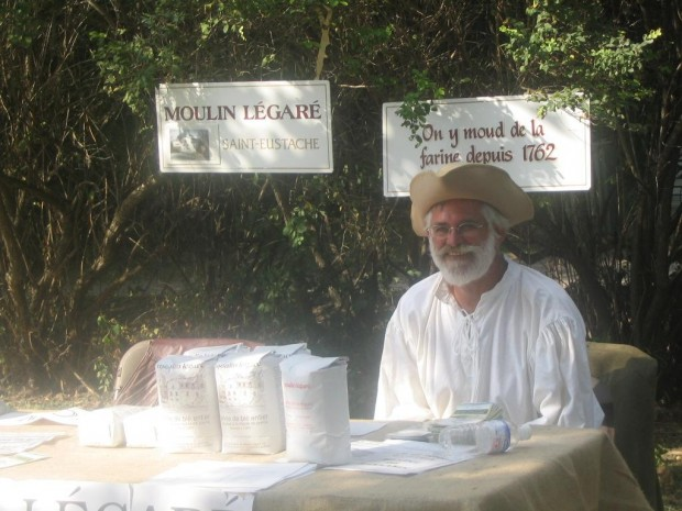 Pierre-Paul Renaud, sporting a white beard, a beige three-cornered hat and a white shirt, sits outside the mill behind a flour sale table.