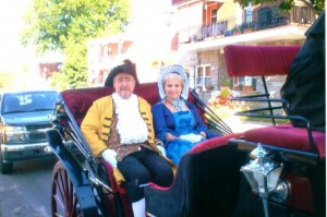 Ernest Labelle, wearing a three-cornered hat, and Marthe Beausoleil, wearing a bonnet, seated in a buggy.