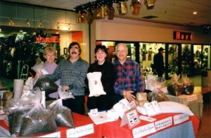 Four volunteers stand behind a table holding flour bags in this photo taken at a shopping mall decorated for Christmas.