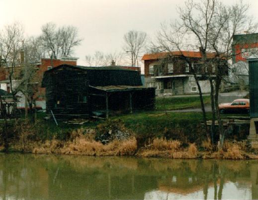 Wide shot of a darkened, weathered building next to a river.