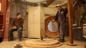 Wide shot of Martin Trudel sitting on the left, looking at Daniel Saint-Pierre standing on the right side of the photo, dressing the lower millstone.