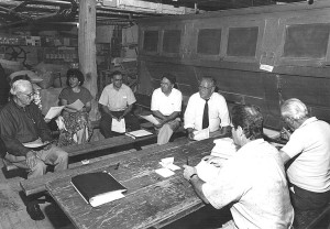 Black and white photo of seven board members sitting in a circle on wooden benches, holding sheets of paper.