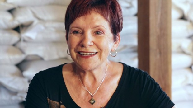 Bust shot of Lise Tremblay with short red hair and earrings, smiling at the camera.