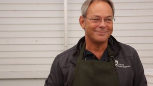 Close-up of Patrice Paquette with grey hair and glasses, wearing a green apron, and smiling at the camera.