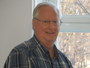 Close-up of Roger Pomerleau with white hair, wearing a plaid shirt, standing in front of a window.