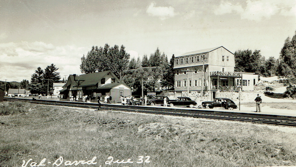 Postcard showing Auberge La belle Chaumière in Val-David, with the railway tracks, Val-David Station and 1940s automobiles.
