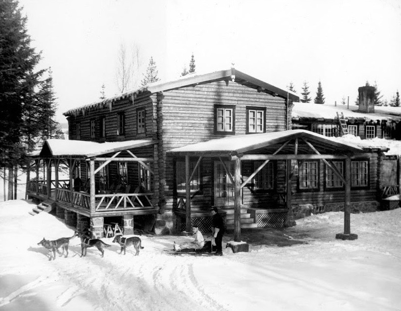 Black and white photo of Auberge La Sapinière in winter 1937; a dogsled is standing in front of the log-built lodge.