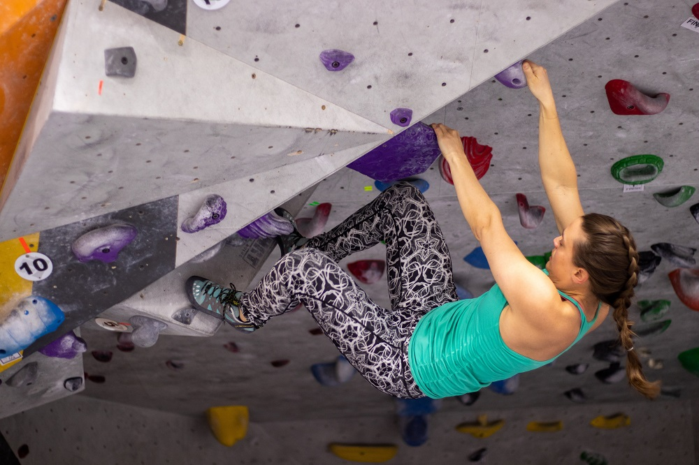 A young woman using hands and feet to hang on to holds resembling handholds on an artificial climbing wall.