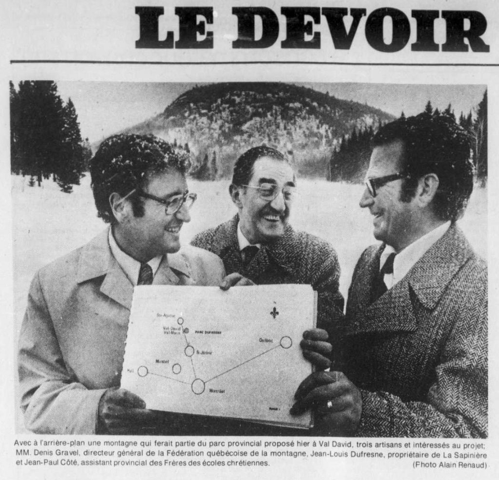Extract from Le Devoir newspaper showing three men holding onto a plan of the projected Val-David Park.
