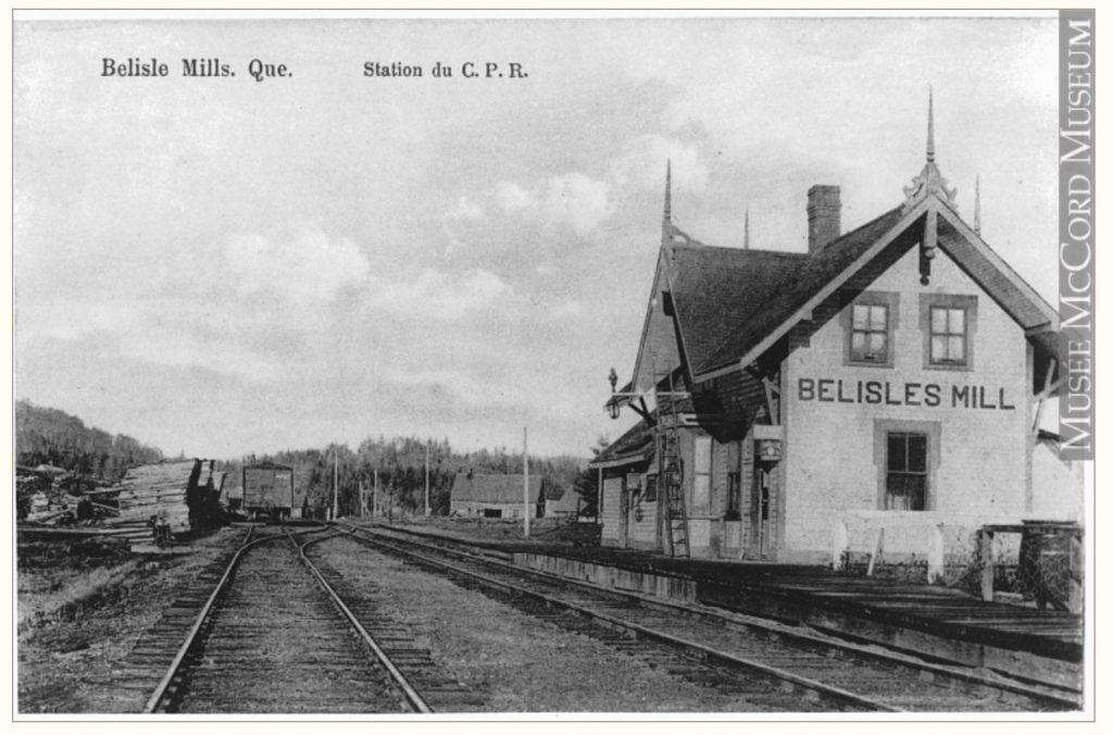 Carte postale ancienne illustrant la gare ferroviaire de Bélisle's Mills; on y remarque l'édifice, les voies ferrées, les tas de bois prêts pour l'expédition.