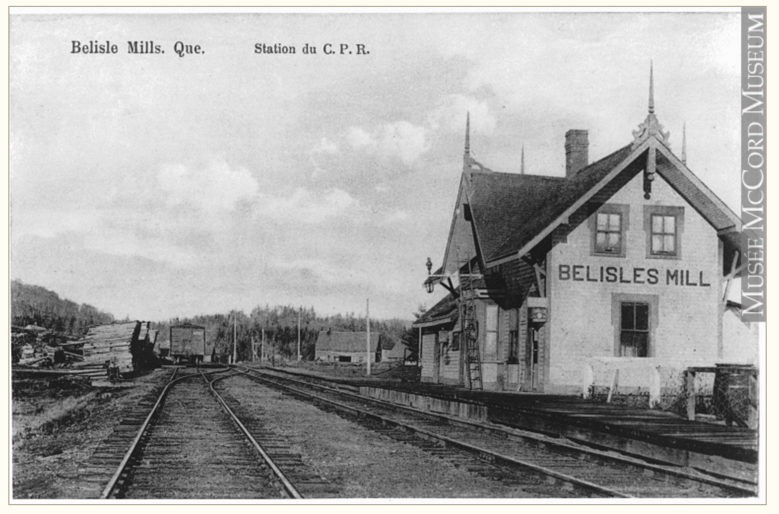 Vintage postcard showing the Bélisle's Mills Railway Station; apart from the building, the railway tracks can be seen and stacks of wood ready for loading.