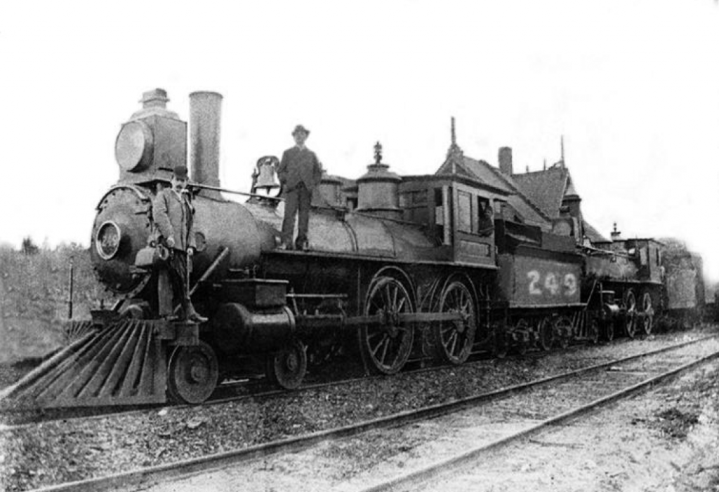 Old photograph of a men standing on the locomotive of the train up North at St-Jérôme Station in 1876.