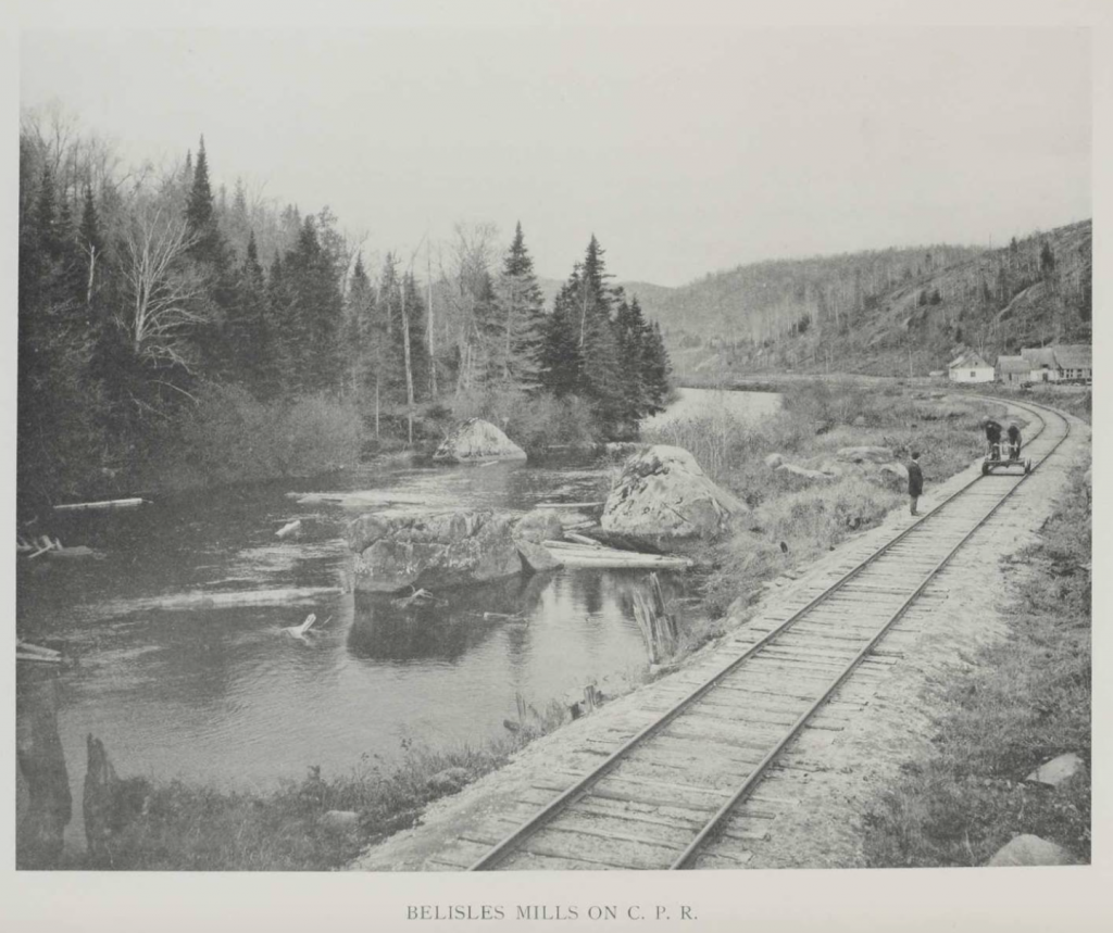 Three men on the railway tracks beside the North River, in the countryside near Val-David village. One man is standing next to the tracks, while the other two are operating a handcar, a rail vehicle used to inspect the tracks.