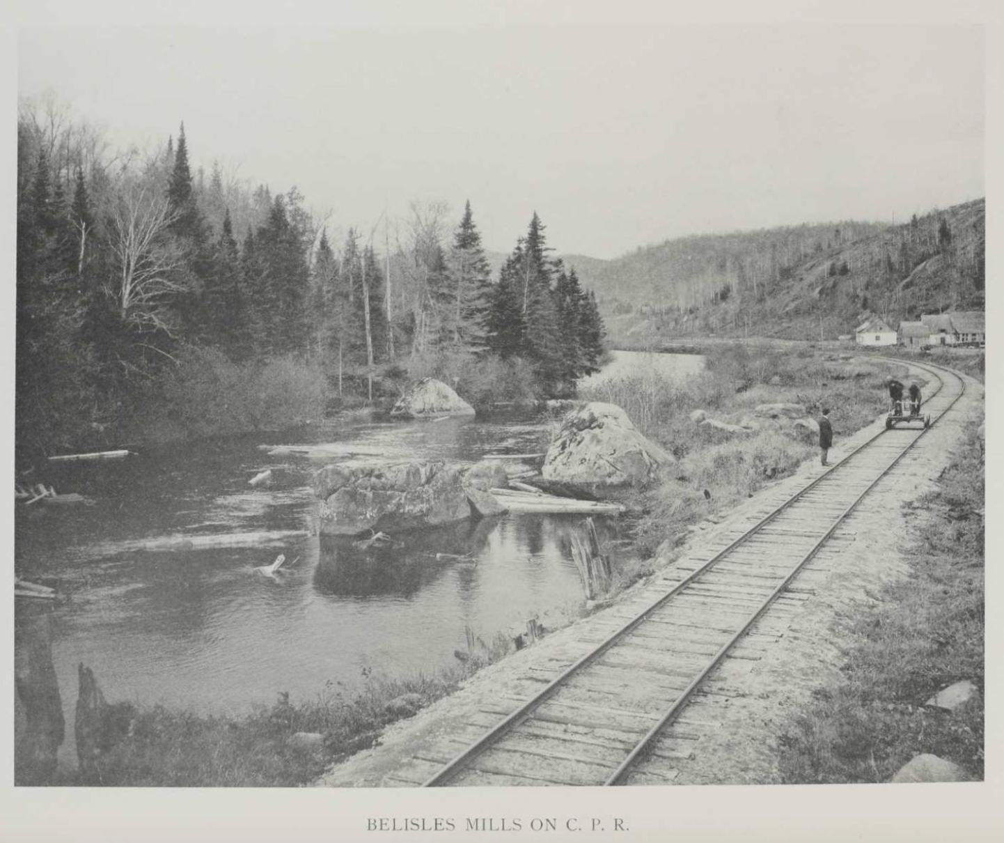 Trois hommes sur la voie ferrée, au bord de la Rivière-du-nord, dans la campagne à proximité du village de Val-David. Un des hommes est debout au bord de la voie ferrée, les deux autres sur un petit wagonnet qui sert à l'entretien des voies.