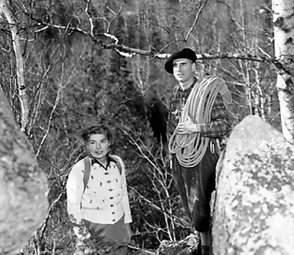 John Brett and his wife in the forest in 1947; John is wearing a beret and holding a climbing rope.