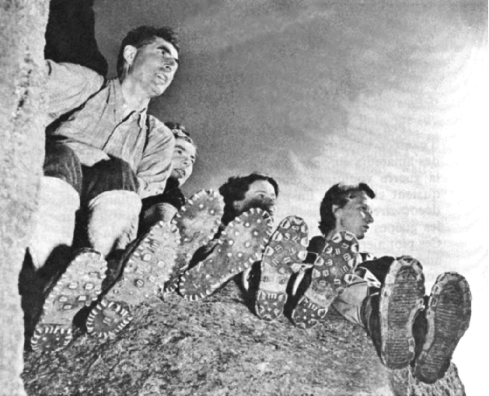Four people seated on the summit of a rock face.