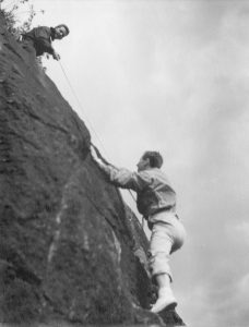 Two climbers, one at the top of the rock face holding a rope by means of which the second climber is still ascending.