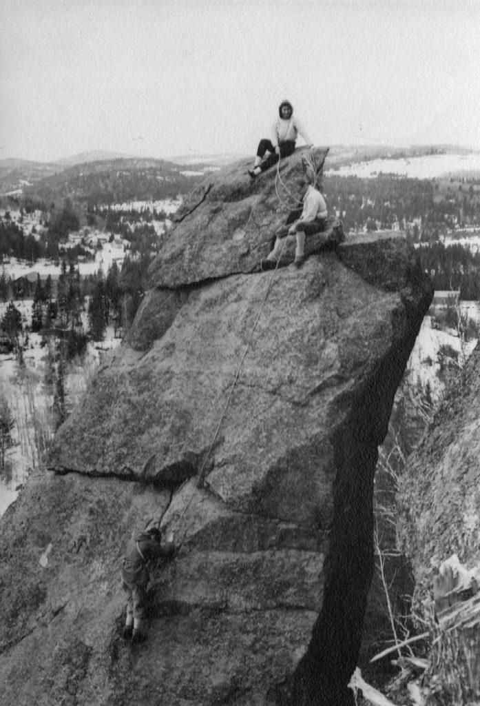 Trois grimpeurs, deux au sommet d'un rocher et une autre personne en train de le grimper en hiver (au loin la campagne est blanche de neige).