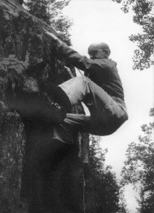 A climber on a rock face in Val-David who, although attached by a rope, does not seem to have any other equipment.