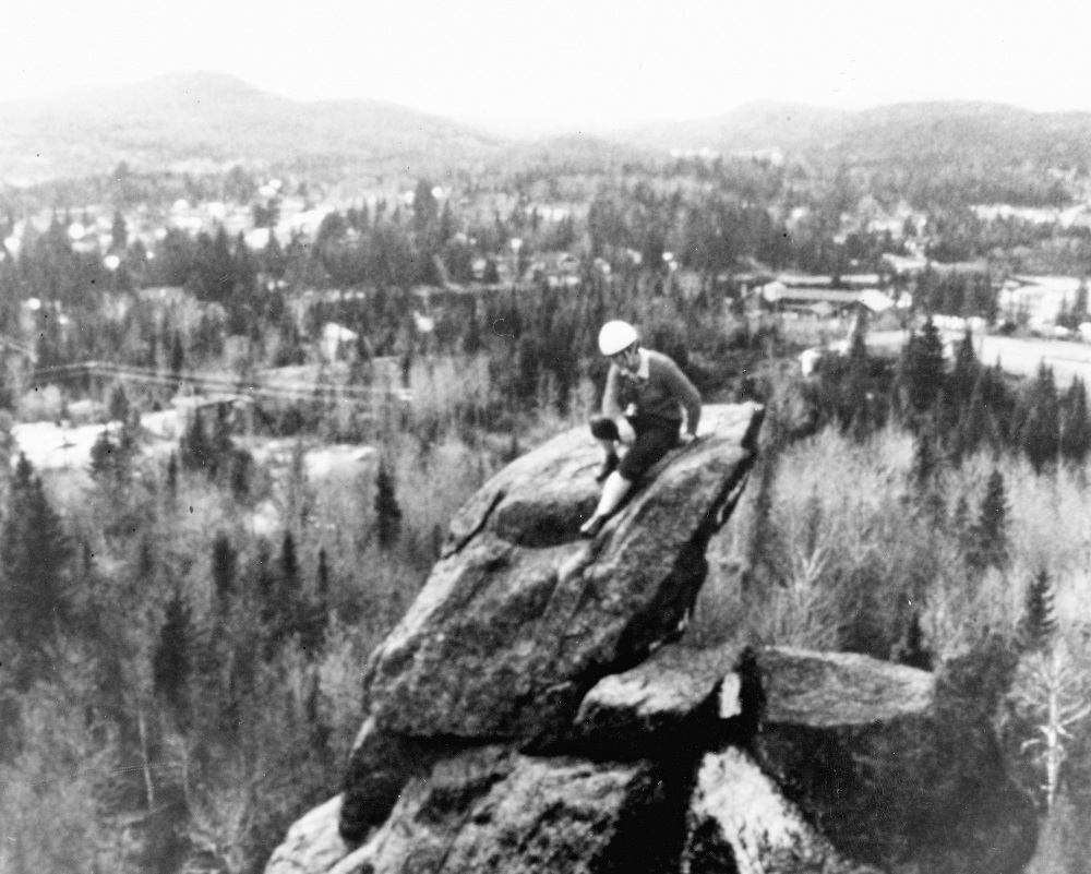 A woman sits on the top of a high rock. In the background is the countryside of Val-David.
