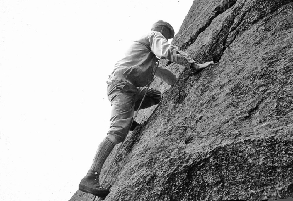 John Brett climbing an inclined rock face in the mountains.