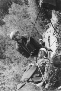 View from above of two men on a rock face in mid-descent; one is strapped to a stretcher and the other is assisting the descent by means of ropes.