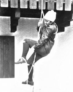 A young female novice climbing on a rope attached to a beam at Auberge le Rouet in Val-David.
