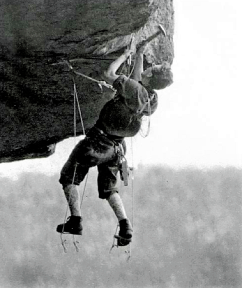 A vintage photo of a climber suspended in mid-air, supported by straps and a short ladder, who is hammering in a piton against a background of sky and the treetops.