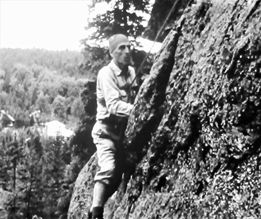 Vintage photo of a climber hanging onto a rock face with hands and feet, against a background of sky and treetops.