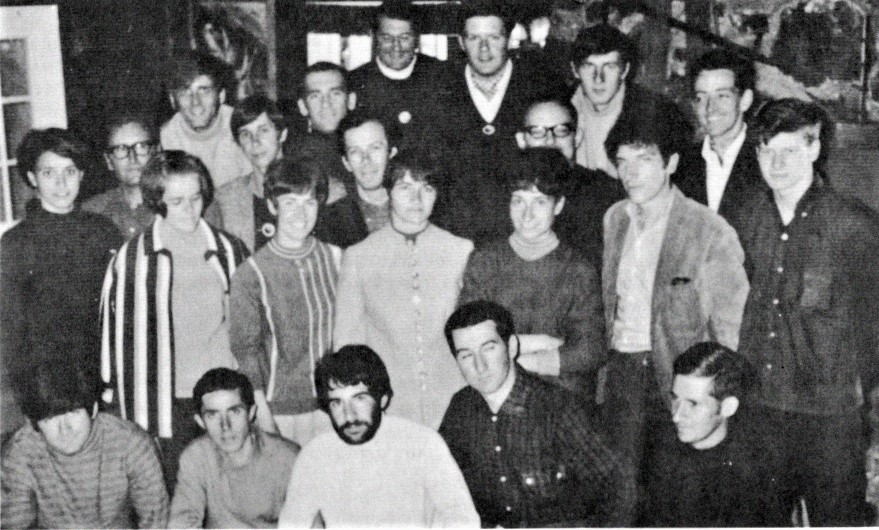 Black and white photo showing a group of about 20 people gathered in a room.