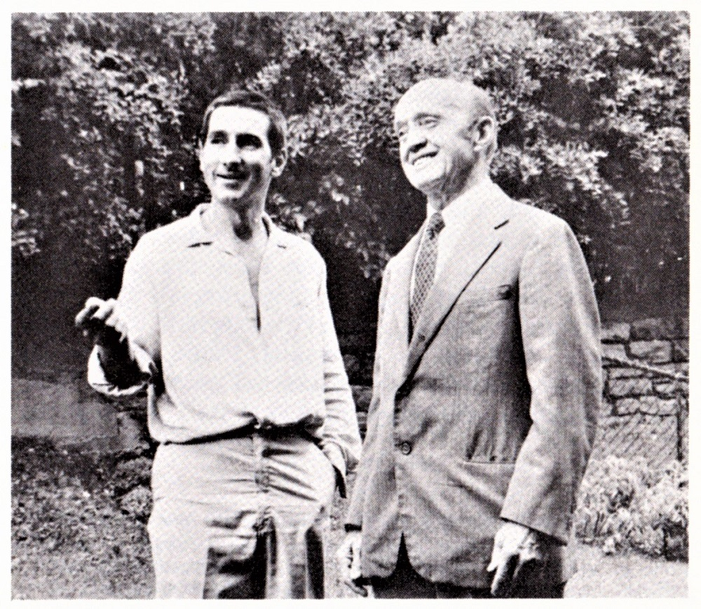 Vintage photo showing two men talking together; the man at left is pointing at something unseen in front of them.
