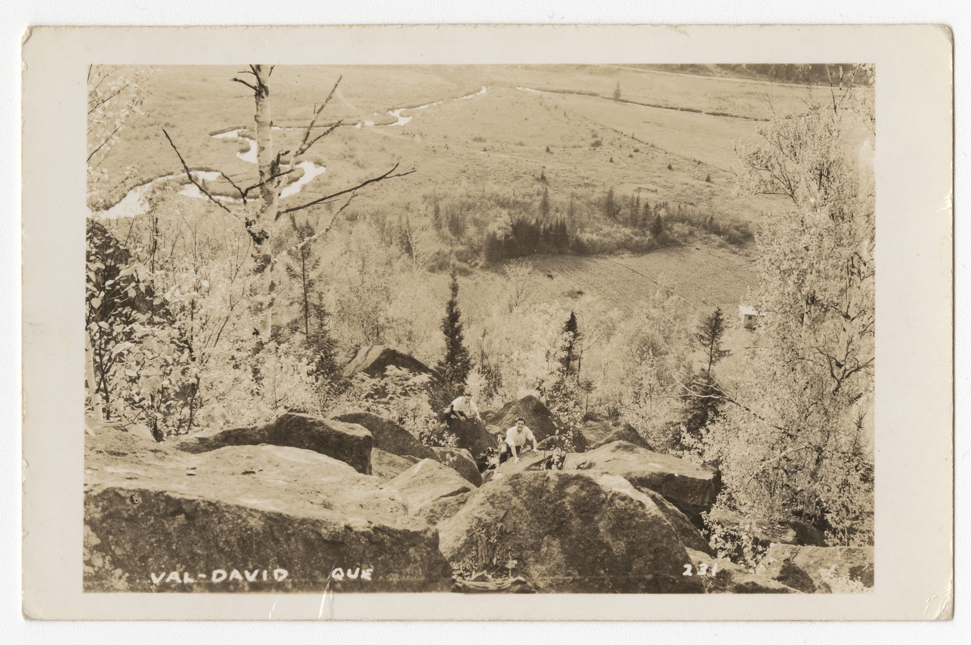 Vintage postcard looking down from a summit; two men are climbing up over a series of boulders. In the background is part of the valley of Val-David.