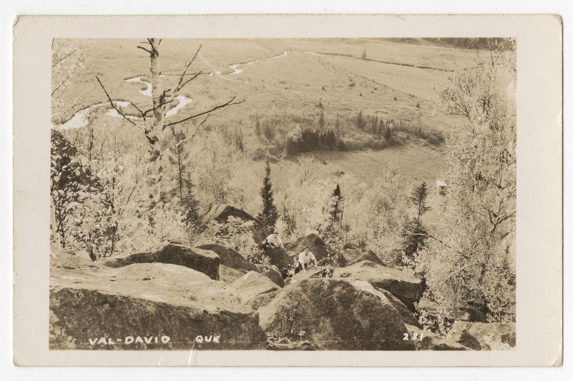 Carte postale prise en plongée depuis un sommet; deux hommes grimpent un amoncellement de rochers. En arrière-plan une partie de la vallée de Val-David.