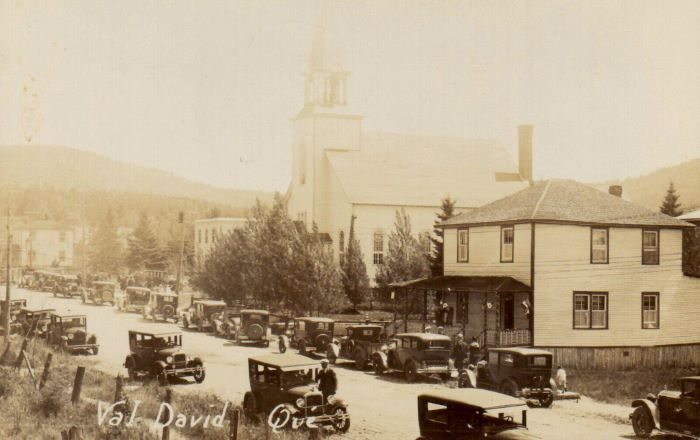View of the village of Val-David in 1929 showing the main street. the church and old cars.