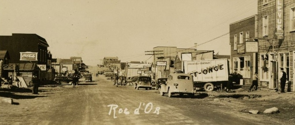 Sepia photograph of an unpaved street lined with buildings on both sides. On the right side, several cars and a truck bearing the inscription St-Onge are visible.