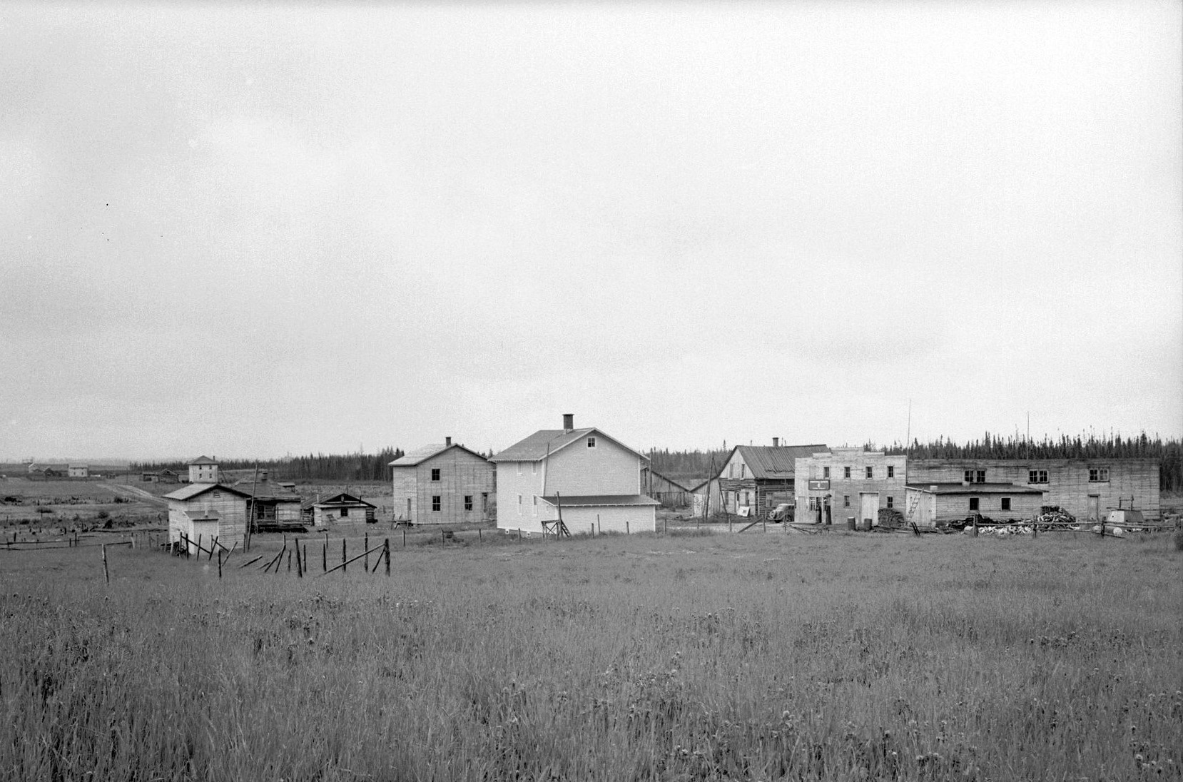 Black and white photograph of a hamlet of about ten buildings, made of logs and planks, surrounded by a field. In the background, a forest.