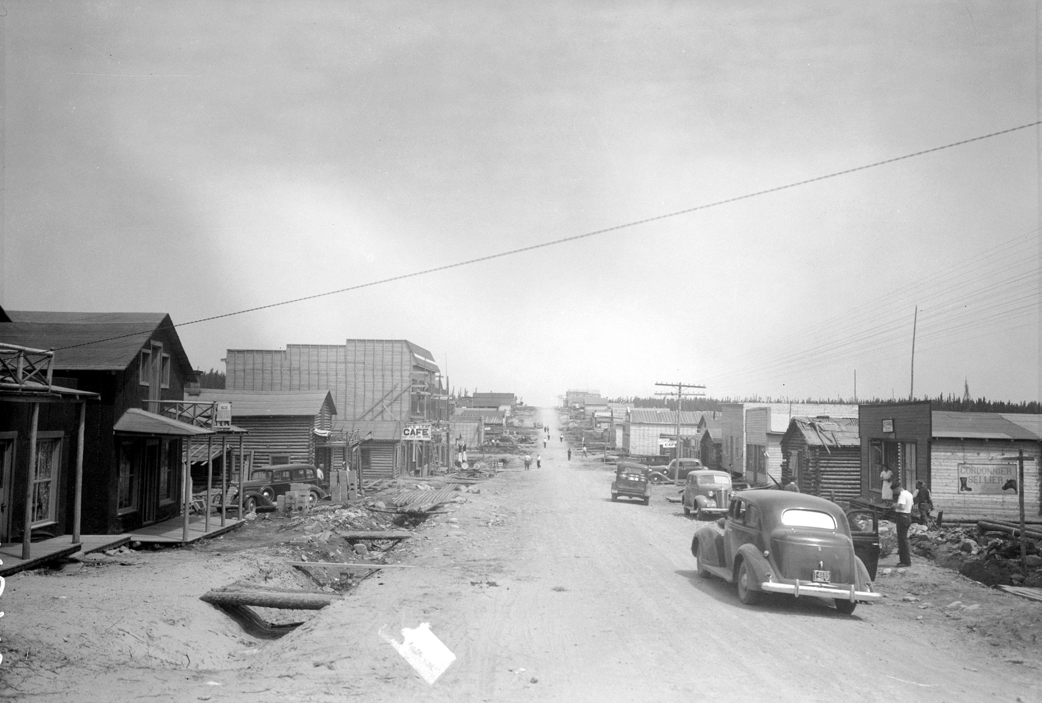 """Black and white photograph of a gravel road lined with plant and log buildings. On the right, signs """"Paris Cafe"""" and """"Royal Restaurant"""". In the foreground on the right, the front ends of two cars."""