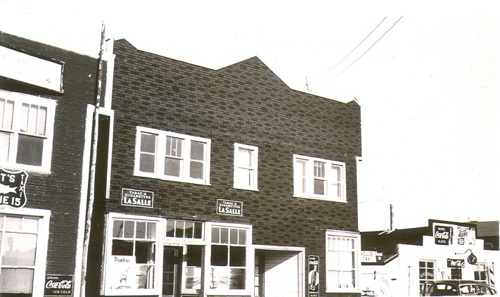 Black and white photograph of a Boomtown-façade two-storey building covered with tar paper. Two