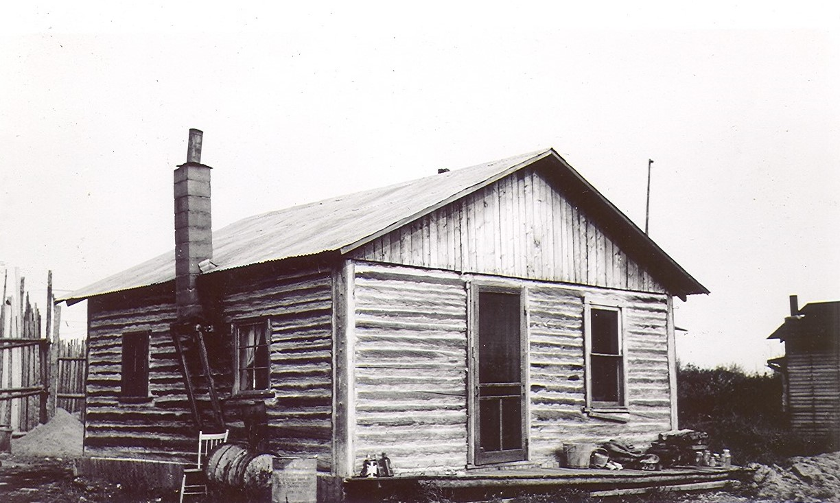 A black and white photograph of a rudimentary log cabin with three windows and a door. On the left, a wobbly chimney.