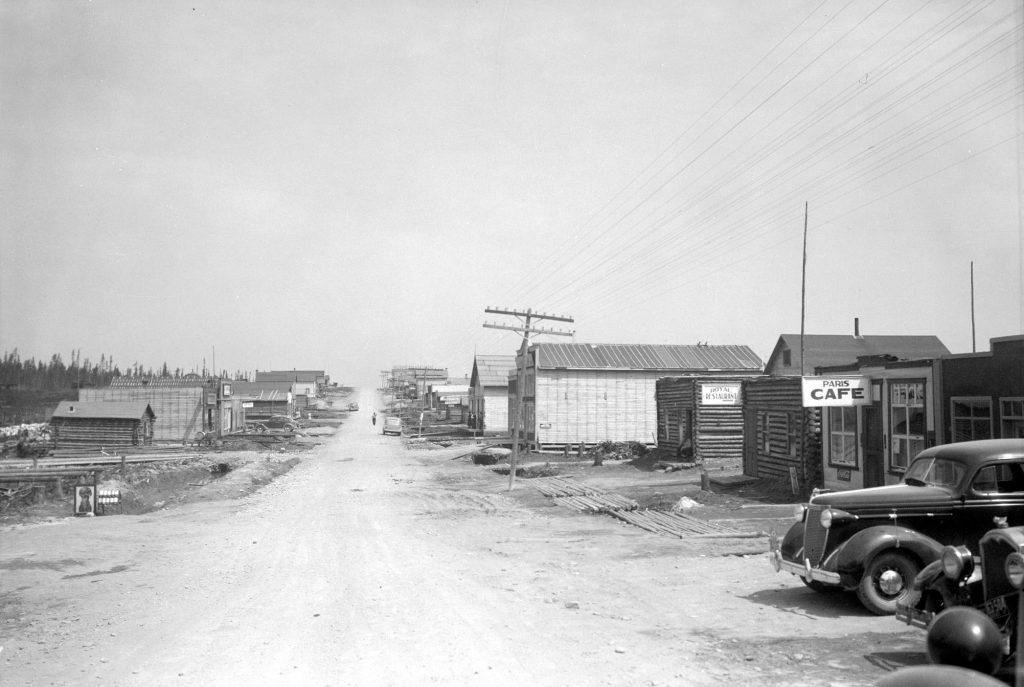 Photographie en noir et blanc d'une route de gravier bordée de bâtiments de planches ou en bois rond. À droite, les affiches « Paris Cafe » et « Royal Restaurant ». À l'avant-plan, à droite, la devanture de deux voitures.