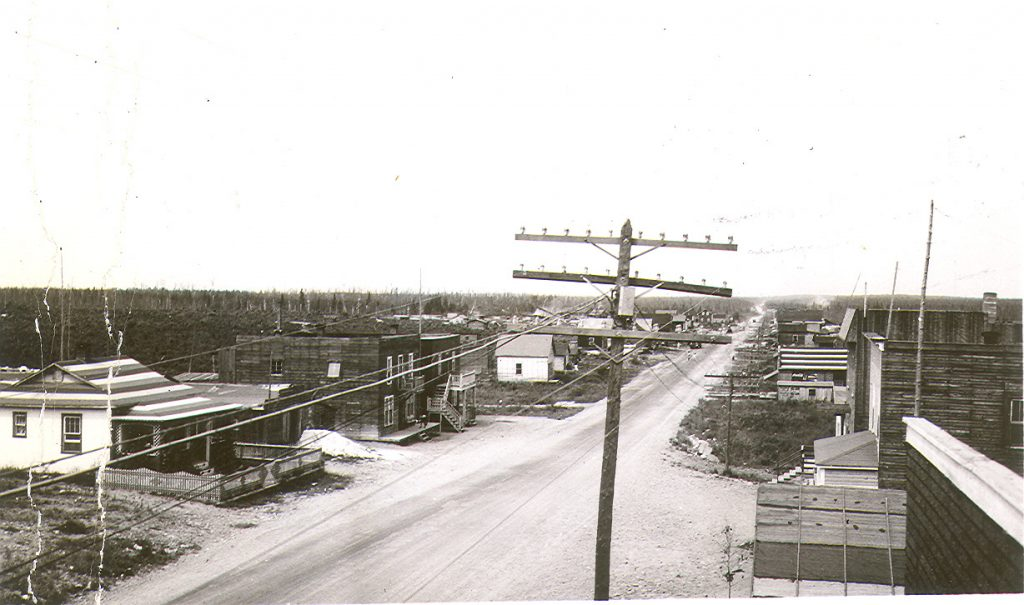 Black and white photograph of a gravel road lined with plank buildings. In the foreground, a pole bearing wires. In the background, a field and a coniferous forest.