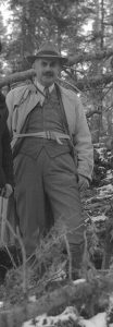 Black and white photograph of a man in a suit, with a hat and a brush moustache, posing in a forest.