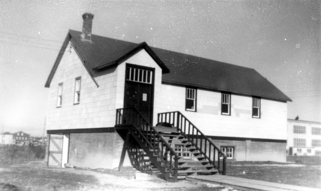 Black and white photograph of a two-storey white church. A staircase, on which a dog is asleep, leads to the main door. On the side, an open door gives access to the basement. In the background on the right, the Catholic primary school.