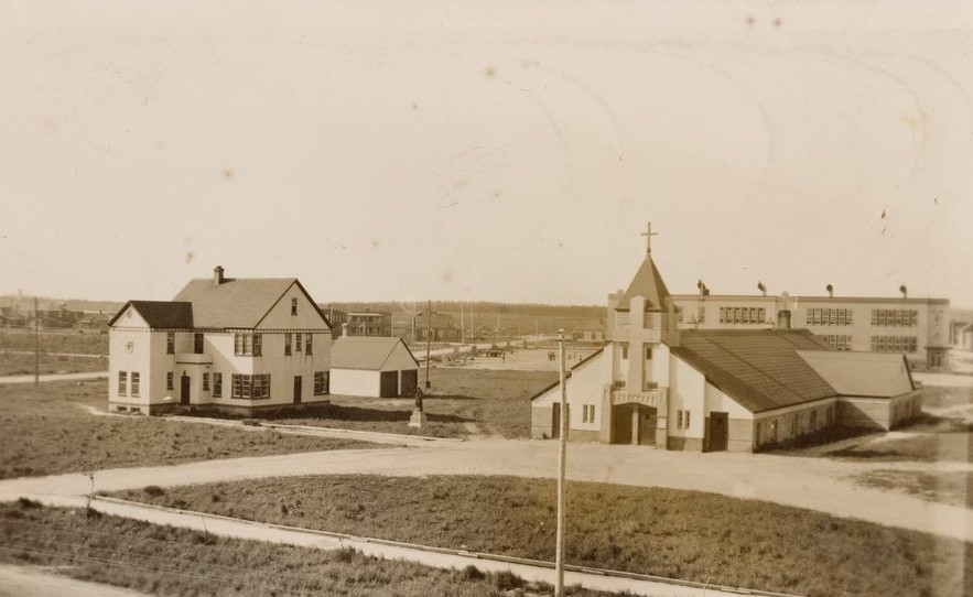 Sepia photograph of the presbytery and the church. The church is low in height and a large cross overhangs the main entrance. In the background, the Catholic primary school.