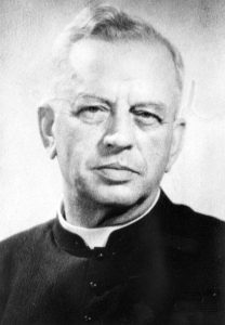 Black and white photograph of an elderly man in a black shirt and Roman collar.