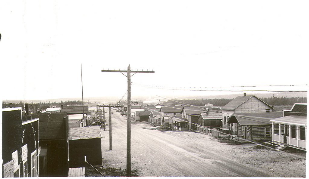 Probably taken from the roof of a building, a black and white photograph of a gravel road lined with wooden log and plank buildings. A forest is visible in the background.