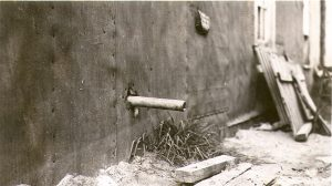 Black and white photograph of a pipe coming out of a building covered with tar paper and spilling its contents onto wooden planks. In the background, a pile of wood.