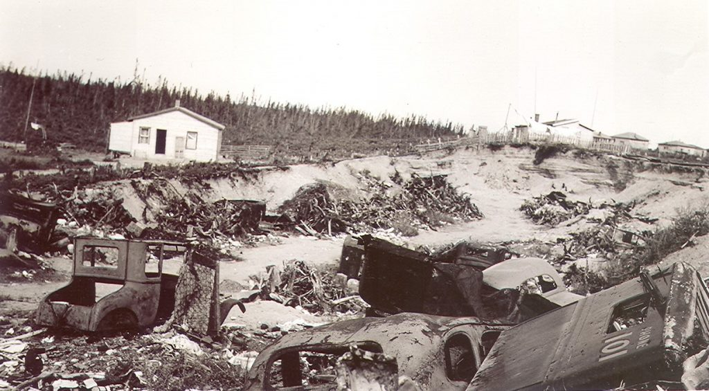 Black and white photograph of a sand pit filled with rusted car bodies and a variety of waste. In the background, several residences behind a fence.